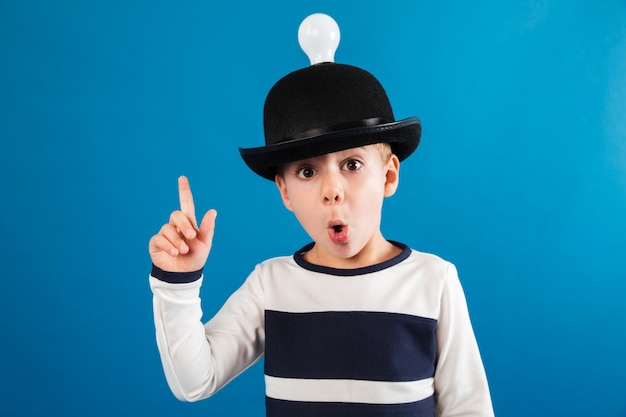 Shocked young boy in hat with lightbulb having idea