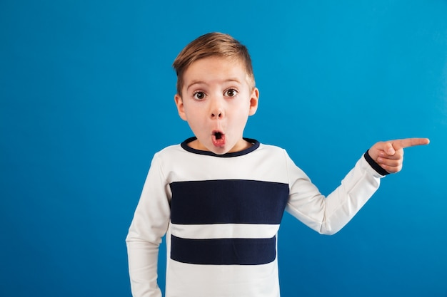 Shocked young boy in sweater pointing away