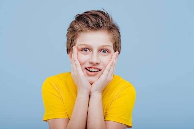 파란색 벽, 복사 공간에 고립 된 노란색 티셔츠에 얼굴에 손으로 충격을 된 어린 소년