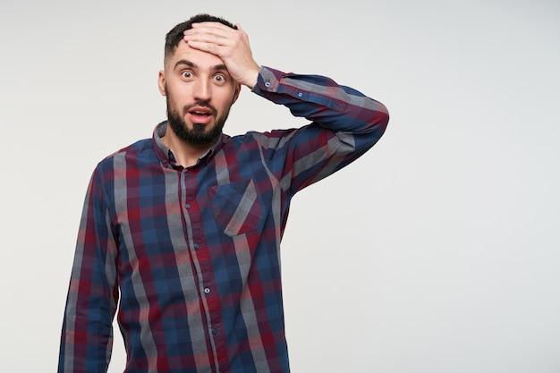 Шокированный молодой кареглазый бородатый брюнет в клетчатой рубашке с изумлением смотрит и держит ладонь на лбу, стоит над белой стеной