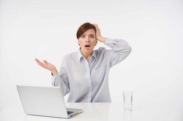 Scioccata giovane donna dai capelli castani con taglio di capelli corto alla moda stringendo la testa con la mano alzata e arrotondando con stupore i suoi occhi, isolati su bianco