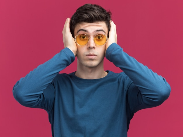 Il giovane ragazzo caucasico brunetta scioccato in occhiali da sole mette le mani sulle orecchie sul rosa