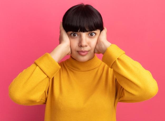La giovane ragazza caucasica castana scioccata chiude le orecchie con le mani sul rosa