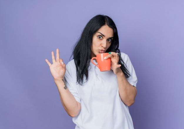 ショックを受けた若いブルネットの白人の女の子は、紫色の壁に分離されたカップとジェスチャーokハンドサインを保持します