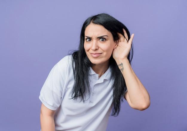 La giovane ragazza caucasica castana scioccata tiene la mano vicino all'orecchio isolato sulla parete viola