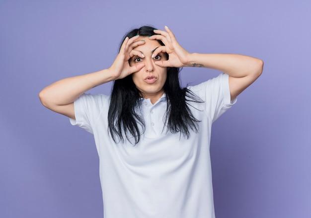 Шокированная молодая кавказская девушка брюнетка открывает глаза пальцами, изолированными на фиолетовой стене