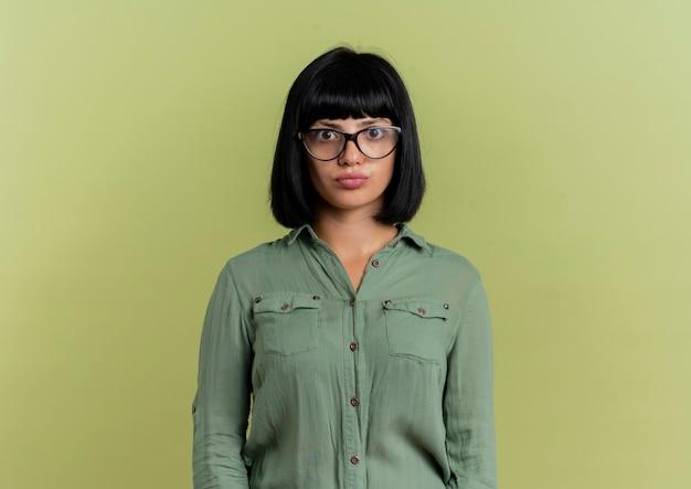 Ragazza caucasica castana giovane scioccata in vetri ottici si leva in piedi isolato su priorità bassa verde oliva con lo spazio della copia