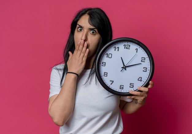 La giovane ragazza caucasica castana scioccata mette la mano sulla bocca e tiene l'orologio isolato sulla parete rosa