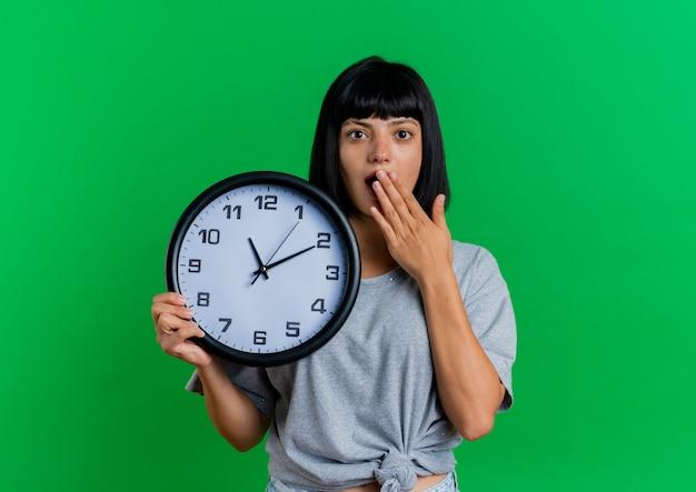 La giovane ragazza caucasica castana scioccata mette la mano sulla bocca e tiene l'orologio
