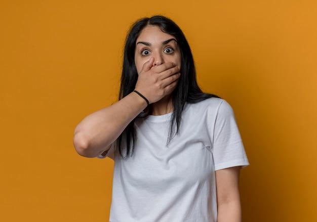 ショックを受けた若いブルネットの白人の女の子は、オレンジ色の壁に孤立して見える口に手を置きます