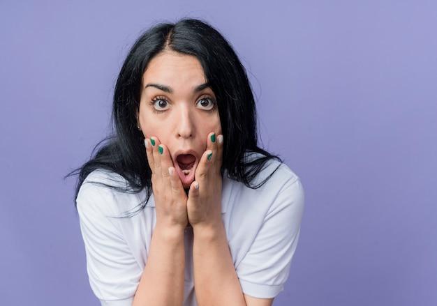 La giovane ragazza caucasica castana scioccata mette le mani sul fronte isolato sulla parete viola