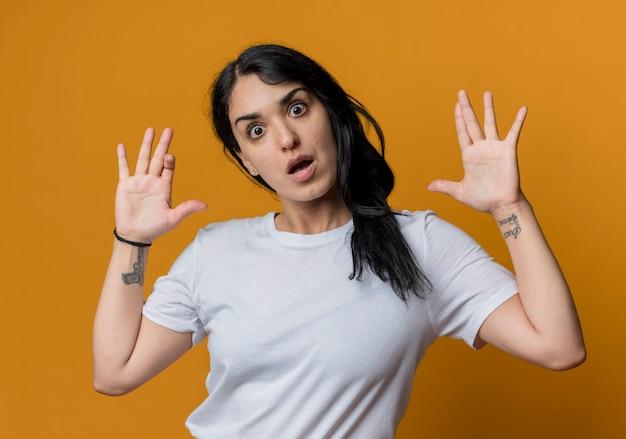 La giovane ragazza caucasica castana scioccata sta con le mani alzate isolate sulla parete arancione