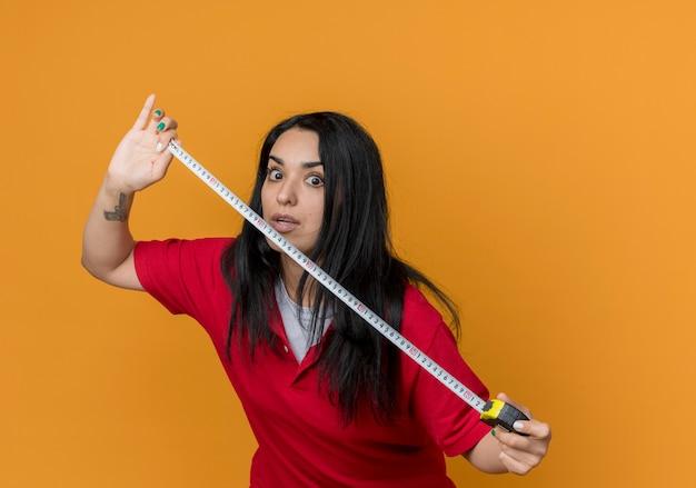 La giovane ragazza caucasica castana scioccata indossa la camicia rossa tiene il metro a nastro isolato sulla parete arancione