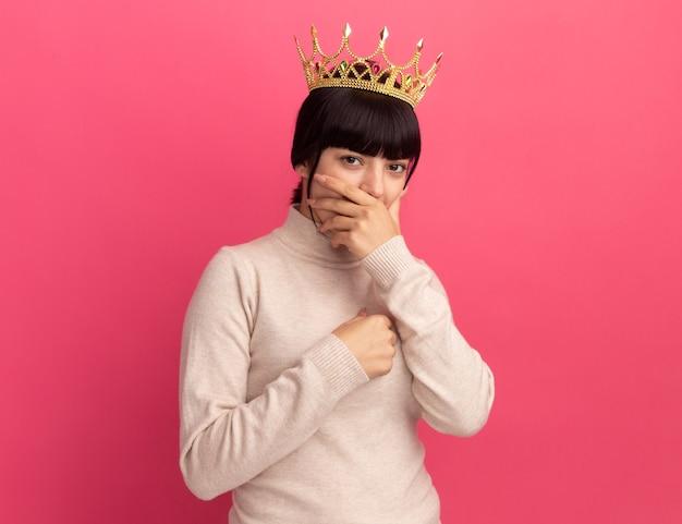 왕관을 쓴 젊은 갈색 머리 백인 소녀가 손을 입에 대고 복사 공간이 있는 분홍색 벽에 격리된 가슴을 잡고 있습니다.