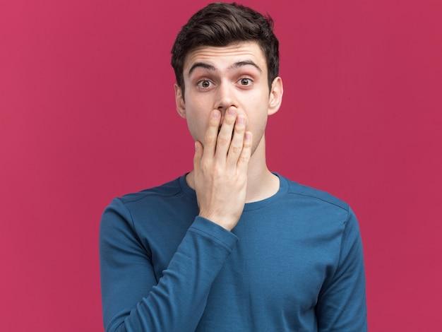 충격을 받은 젊은 갈색 머리 백인 남자는 복사 공간이 있는 분홍색 벽에 격리된 입에 손을 얹습니다.