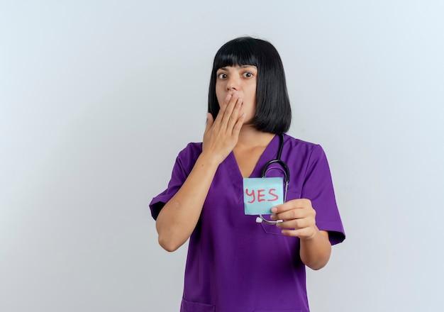 Il giovane medico femminile del brunette scioccato in uniforme con lo stetoscopio mette la mano sulla bocca e tiene la nota di sì