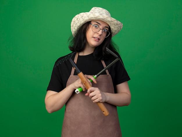 光学ガラスと制服を着たガーデニング帽子のショックを受けた若いブルネットの女性の庭師は、緑の壁に分離されたくわ熊手と熊手を保持します