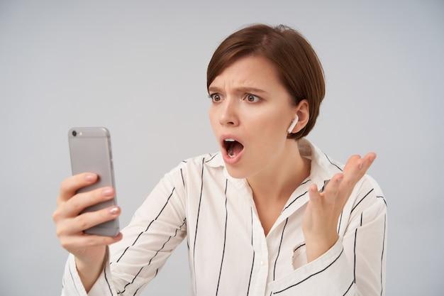 짧은 트렌디 한 머리가 제기 손에 휴대 전화를 유지하고 넓은 눈과 입으로 화면을보고 충격을받은 젊은 갈색 머리 여자는 분홍색 흰색에 고립
