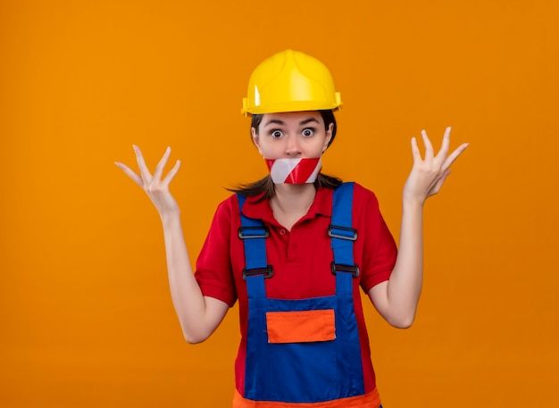 La bocca scioccata della ragazza del giovane costruttore sigillata con nastro adesivo di avvertimento solleva le mani su sfondo arancione isolato