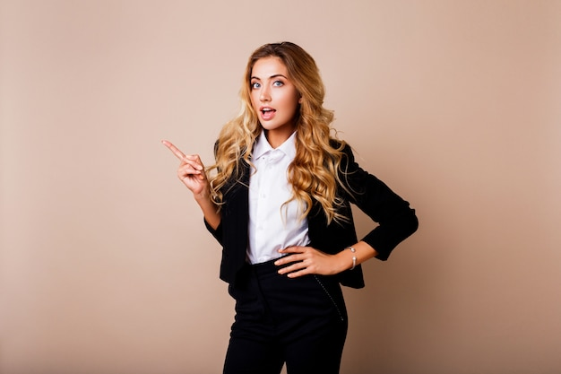 ショックを受けた若いビジネス女性やベージュの壁を越えてポーズスタイリッシュなスーツを着た従業員。
