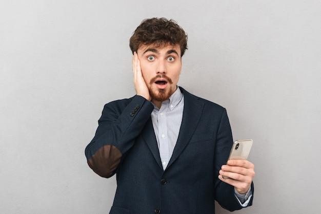 Шокированный молодой бизнесмен в костюме, стоящий изолированно над серым, держа мобильный телефон