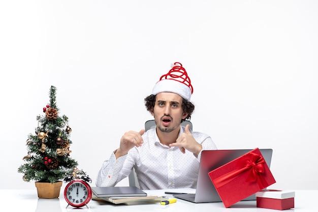 Шокирован молодой бизнесмен с забавной шляпой санта-клауса и празднует рождество в офисе на белом фоне