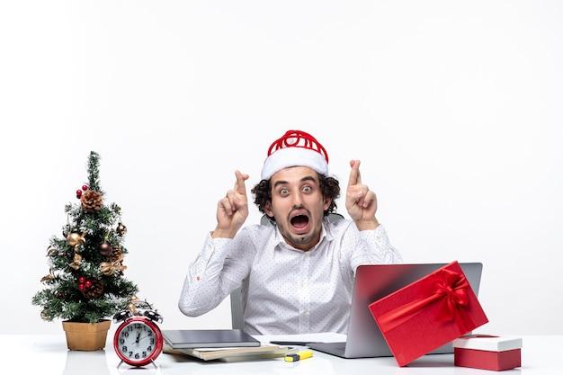 Шокирован молодой бизнесмен со смешной шляпой санта-клауса, скрестив пальцы на удачу в офисе на белом фоне