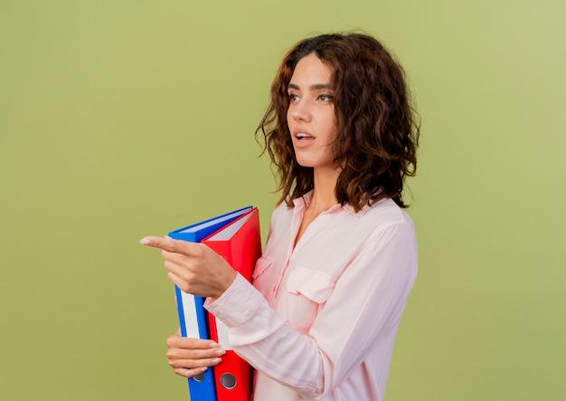 ショックを受けた若い白人の女の子は、コピースペースで緑の背景に分離された側を見て、指しているファイルフォルダを保持します
