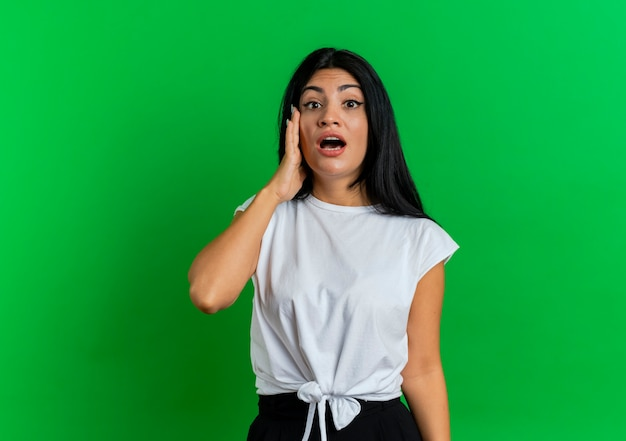 La giovane ragazza caucasica scioccata mette la mano sulla ricerca del viso