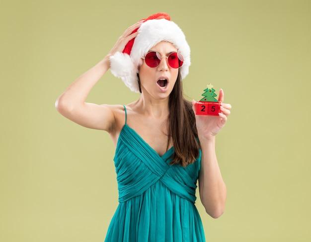 La giovane ragazza caucasica scioccata in occhiali da sole con il cappello della santa mette la mano sulla testa e tiene l'ornamento dell'albero di natale che esamina il lato
