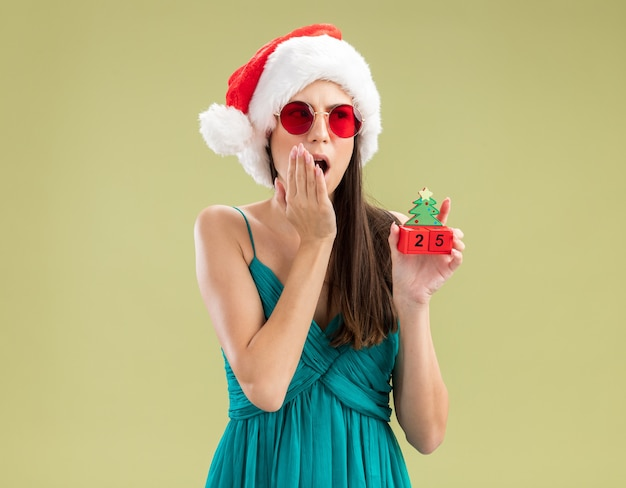 Shocked young caucasian girl in sun glasses with santa hat puts hand on mouth and holds christmas tree ornament looking at side