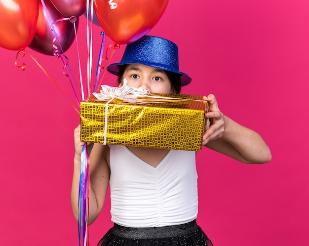 Shocked young caucasian girl with blue party hat holding gift box and helium balloons isolated on pink wall with copy space