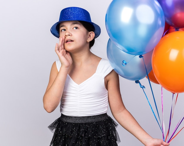 Shocked young caucasian girl with blue party hat holding helium balloons and looking up isolated on white wall with copy space