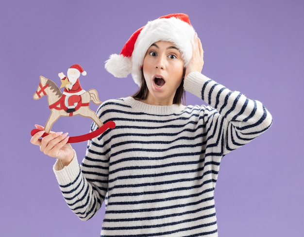 Shocked young caucasian girl with santa hat puts hand on head and holds santa on rocking horse decoration isolated on purple wall with copy space