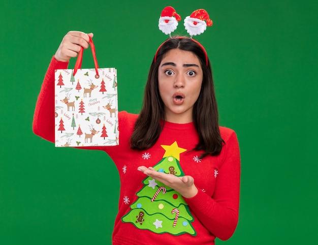 Шокированная молодая кавказская девушка с ободком санта-клауса держит и указывает на бумажный подарочный пакет, изолированный на зеленом фоне с копией пространства