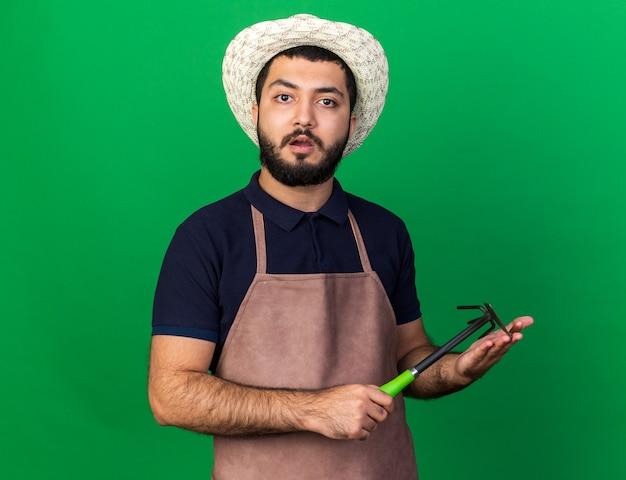 Scioccato giovane maschio caucasico giardiniere che indossa cappello da giardinaggio tenendo il rastrello zappa isolato sulla parete verde con spazio di copia
