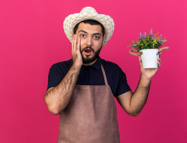 Shocked young caucasian male gardener wearing gardening hat puts hand on face and holds flowerpot isolated on pink wall with copy space