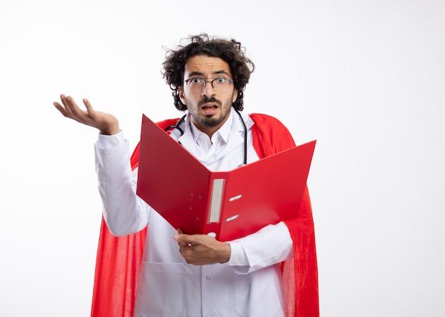 赤いマントと首の周りに聴診器で医者の制服を着て光学メガネでショックを受けた若い白人男性は、上げられた手で立って、コピースペースでファイルフォルダーを保持します