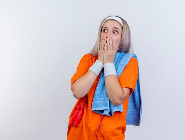 중괄호와 어깨에 수건을 들고 머리띠 팔찌를 착용하는 목 주위에 밧줄 점프 충격을받은 젊은 백인 스포티 한 소녀가 흰 벽에 측면을보고 입에 손을 넣습니다.