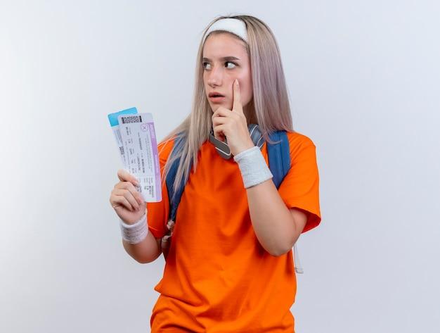 배낭 머리띠와 팔찌를 착용하는 목에 헤드폰으로 충격을받은 젊은 백인 스포티 한 소녀는 얼굴에 손가락을 넣고 흰 벽에 고립 된 측면을보고 항공권을 보유하고 있습니다.