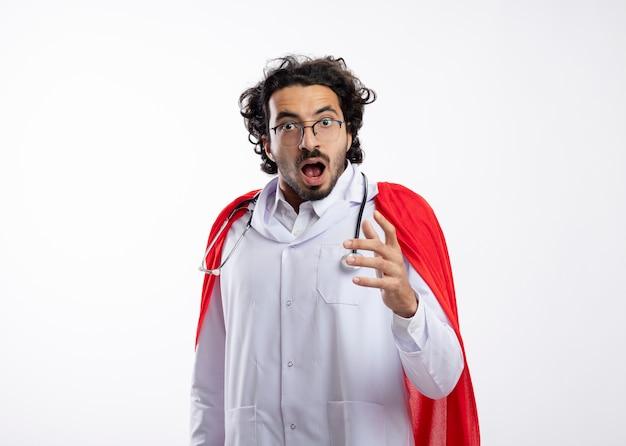 赤いマントと聴診器の周りに赤いマントと聴診器を身に着けている光学メガネのショックを受けた若い白人のスーパーヒーローの男は手で見た目とポイント