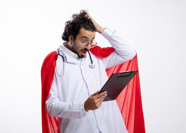 빨간 망토와 목에 청진기로 의사 유니폼을 입고 광학 안경에 충격을받은 젊은 백인 슈퍼 히어로 남자가 머리를 잡고 흰 벽에 클립 보드를보고 손을 넣습니다.