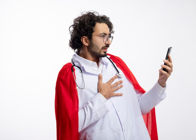 Scioccato giovane supereroe caucasico uomo in occhiali ottici che indossa l'uniforme del medico con mantello rosso e con lo stetoscopio intorno al collo mette la mano sul petto e guarda il telefono con lo spazio della copia