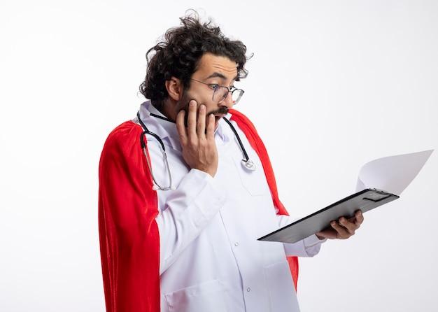 Scioccato giovane supereroe caucasico uomo in occhiali ottici che indossa l'uniforme del medico con mantello rosso e con lo stetoscopio intorno al collo mette la mano sul viso tenendo e guardando gli appunti sul muro bianco