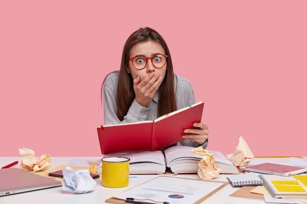 Шокированный молодой студент колледжа держит красный дневник, окруженный толстой открытой книгой, портативный компьютер, удивлен тем, что у него дедлайн задание, пьет кофе