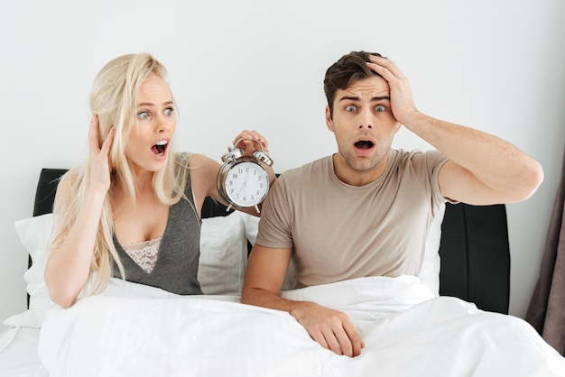 Shocked young couple sitting in bed with opened mouth and holding alarm clock