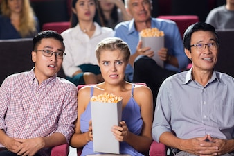 Shocked young couple watching thriller in cinema
