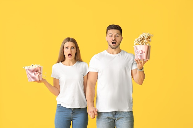 Shocked young couple with popcorn on color background