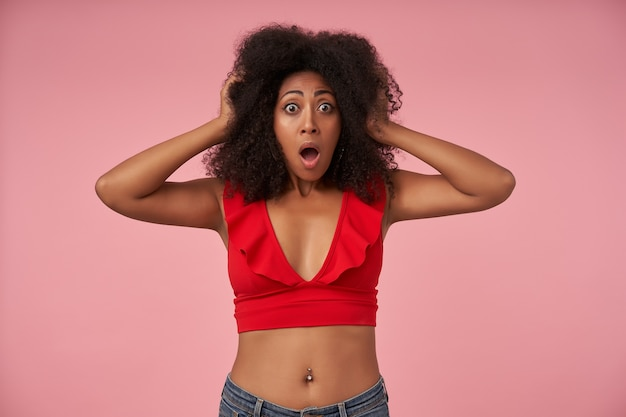 Shocked young curly female with dark skin and belly button piercing standing on pink, with wide eyes and mouth opened, holding head with raised hands
