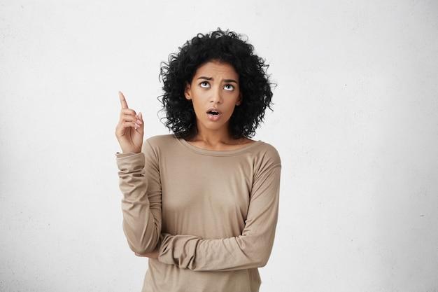 Giovane donna scioccata dalla pelle scura vestita casualmente che mostra qualcosa di sorprendente sopra la sua testa, tenendo la bocca spalancata, in piedi contro il muro bianco